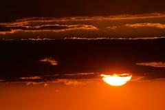 Por do sol com nuvens escuras e o céu vermelho Fotos de Stock Royalty Free