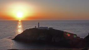 Por do sol com o alargamento da lente no farol sul da pilha - Anglesey, Gales filme