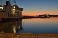 Por do sol com o barco que espera para deixar o porto Imagens de Stock
