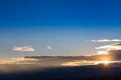 Por do sol com o céu alaranjado e azul acima da terra imagem de stock