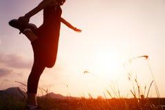 Por do sol com o corredor da mulher do esporte que estica o músculo após a corrida foto de stock royalty free