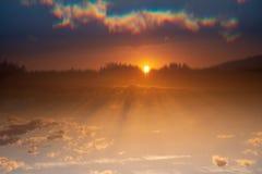 Por do sol com o sol escondido quase e as sombras nas nuvens e no azul imagem de stock