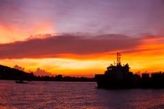 Por do sol com o navio de guerra no mar Fotografia de Stock Royalty Free