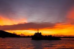 Por do sol com o navio de guerra no mar imagens de stock