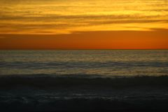 Por do sol com ondas calmas Fotos de Stock