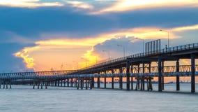 Por do sol com a ponte ao mar imagens de stock royalty free