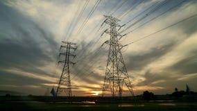Por do sol com a torre da linha elétrica de duas transmissões no campo de almofada filme