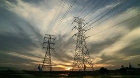 Por do sol com a torre da linha elétrica de duas transmissões no campo de almofada vídeos de arquivo