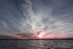 Por do sol cor-de-rosa com as nuvens sobre o mar Foto de Stock