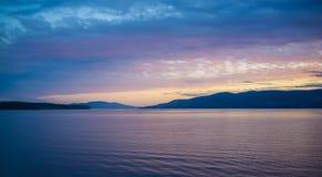 Por do sol cor-de-rosa e alaranjado sobre montes e água em Tasmânia Fotografia de Stock