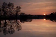Por do sol cor-de-rosa sobre o lago fotos de stock