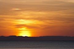 Por do sol cor-de-rosa vermelho sobre o oceano e as montanhas Fotografia de Stock