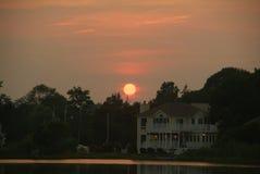 Por do sol da casa do lago Fotos de Stock