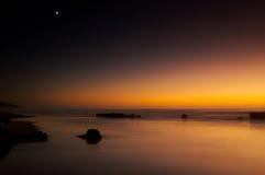 Por do sol da lua do oceano imagem de stock royalty free
