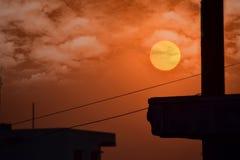 Por do sol da paisagem em construções com céu nebuloso Fotografia de Stock Royalty Free