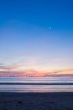 Por do sol da praia com uma meia lua Imagem de Stock Royalty Free