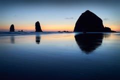 Por do sol da rocha do monte de feno, praia do canhão, Oregon fotos de stock