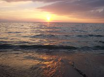 Por do sol de encontro à costa Fotografia de Stock Royalty Free