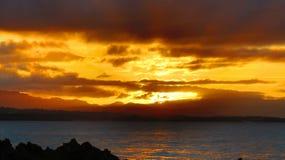 Por do sol de HDR com nuvens e raios de luz alaranjados fotografia de stock royalty free