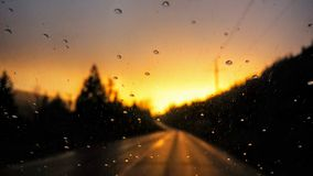 Por do sol de incandescência focalizado em pingos de chuva Fotografia de Stock Royalty Free