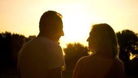 Por do sol de observação da silhueta superior dos pares junto, data romântica no campo imagens de stock royalty free