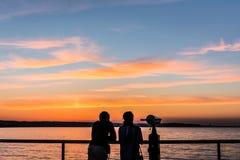 Por do sol de observação dos pares do passeio à beira mar Fotos de Stock