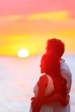 Por do sol de observação dos pares felizes em férias da praia fotos de stock