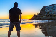 Por do sol de observação do homem sobre Oceano Atlântico Imagens de Stock