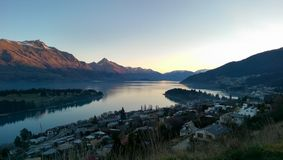 Por do sol de Queenstown com casas e montanhas Imagem de Stock