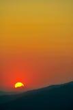 Por do sol distante sobre a escala de montanha mostrada em silhueta Fotos de Stock