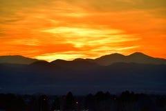 Por do sol do amarelo alaranjado sobre montanhas Imagem de Stock