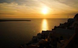 Por do sol do beira-mar com a silhueta da ilha de Santorini em Grécia imagens de stock royalty free