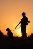 Por do sol do caçador com um cão Imagens de Stock