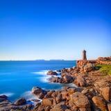 Por do sol do farol de Ploumanach na costa cor-de-rosa do granito, Brittany, França. Imagens de Stock Royalty Free