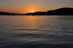 Por do sol do mar com silhueta do barco Fotos de Stock Royalty Free