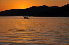 Por do sol do mar com silhueta do barco Imagens de Stock Royalty Free
