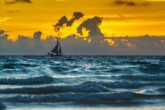 Por do sol do oceano com o barco de navigação branco no horizonte fotografia de stock royalty free