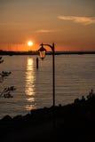 Por do sol do oceano com uma lanterna no foregorund Imagens de Stock Royalty Free