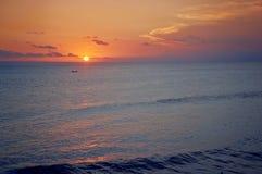 Por do sol do oceano e um barco de pesca Fotos de Stock Royalty Free