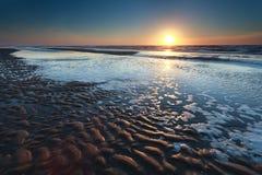 Por do sol do ouro sobre a praia da areia do Mar do Norte na maré baixa imagem de stock royalty free