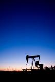 Por do sol do pumpjack do poço de petróleo imagem de stock