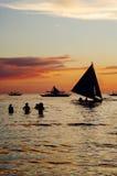 Por do sol dourado bonito sobre barcos e povos de pesca na água Imagem de Stock Royalty Free
