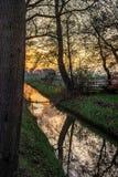 Por do sol dourado cênico sobre um canal na Holanda imagens de stock royalty free