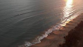 Por do sol dourado da vista aérea sobre o mar com as ondas que deixam de funcionar na costa com reflexões bonitas na água e lo video estoque