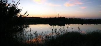 Por do sol dourado de relaxamento em um lago no parque na cidade Imagens de Stock