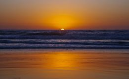 Por do sol dourado, mar agitado, praia dourada imagem de stock