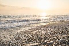 Por do sol dourado no mar, seixos do verão bonito na costa que brilha no sol Fotos de Stock