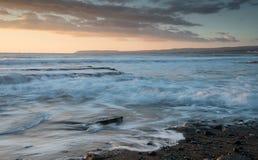 Por do sol dramático bonito sobre uma costa rochosa Fotos de Stock Royalty Free