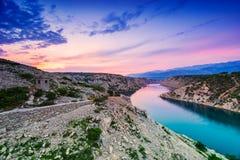 Por do sol dramático colorido sobre o rio e as montanhas em Dalmácia, Croácia imagem de stock royalty free