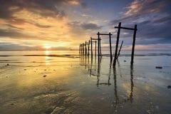 Por do sol dramático com reflexões na praia enlameada Imagem de Stock